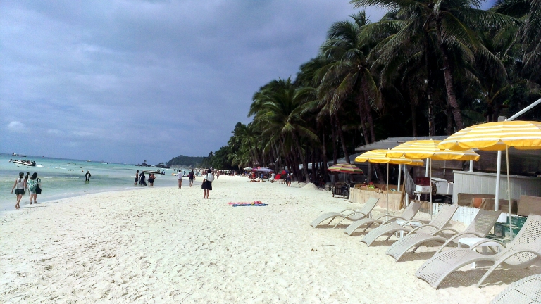 Long stretches of white sand and rows of coconut trees in Boracay