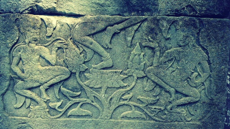 A carving of someone dancing on top of what seems to be a flower