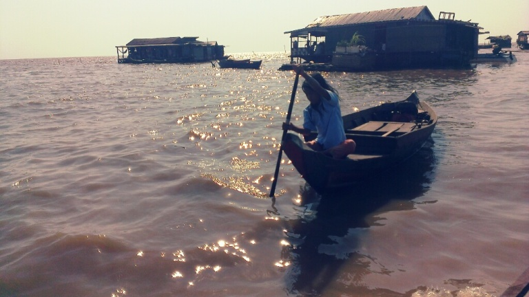 Young girl rowing at the floating village of Tonle Sap