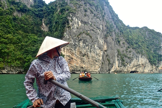 Vietnamese woman rowing in Halong Bay
