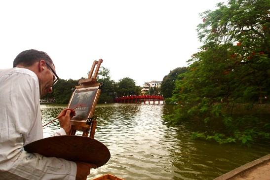 An artist painting the famous Red Bridge of Hoan Kiem Lake