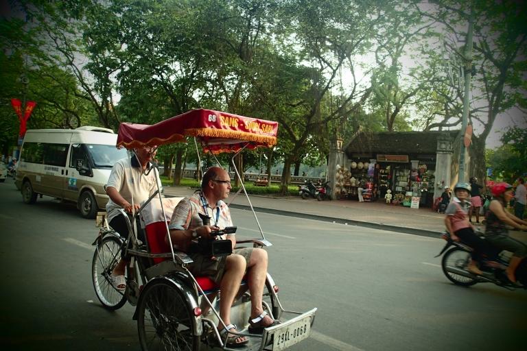 A tourist with a huge camera riding a cycle rickshaw aka cyclo