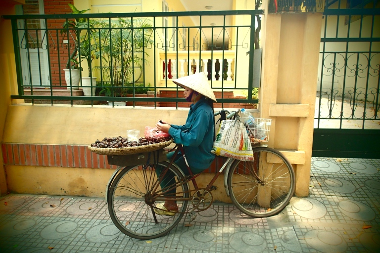 A Vietnamese woman on a bike selling food
